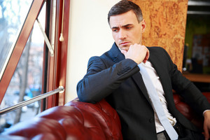 Thoughtful businessman sitting and looking in window at office