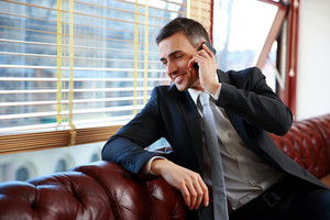 Happy businessman talking on the phone and looking in window at office