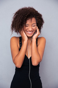 Afro american woman listening music in headphones