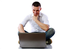 Happy man sitting at the floor with laptop over white background