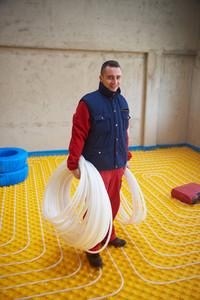 Workers installing underfloor heating system