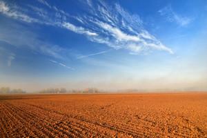 Orange Soil Field Against Blue Sky