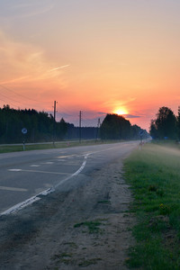 Classic Countryside Landscape With Road Against Dramatic Sunrise