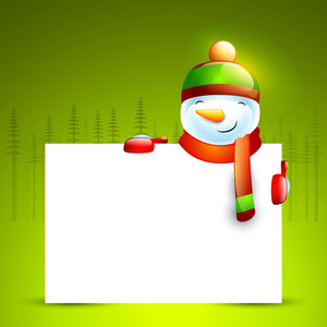 Cute smiling snowman holding blank board on fir trees decorated shiny green background for Merry Christmas celebration.