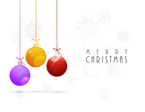 Chirstmas Day celebration with colourful hanging balls and stylish text of Merry Christmas on white background with snowflakes.
