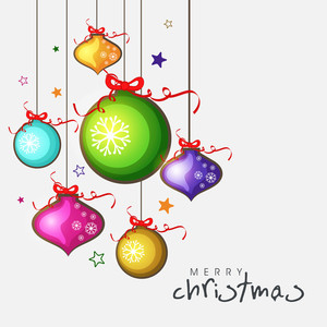 Colorful shiny hanging Xmas balls for Merry Christmas celebration on beige background.