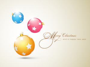 Shiny and colorful stars decorated christmas balls on shiny beige background for Merry Christmas celebrations.