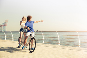 Couple riding on tandem bicycle outdoors