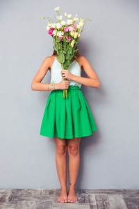 Woman covering her face with flowers