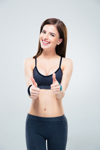 Smiling cute sporty woman showing thumb up