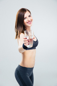 Sporty woman giving glass of water on camera