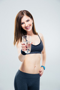 Smiling sporty woman giving glass of water on camera