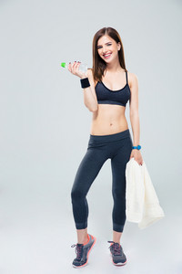 Smiling woman standing with bottle of water and towel