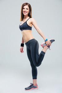 Happy sporty woman stretching leg