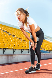 Woman resting after run on stadium