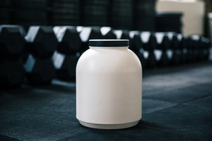 Plastic container with sports nutrition on dumbbells