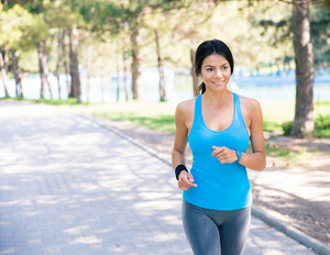 Smiling woman running in park