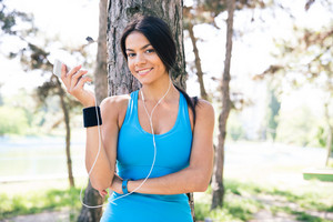 Happy sporty woman holding smartphone outdoors