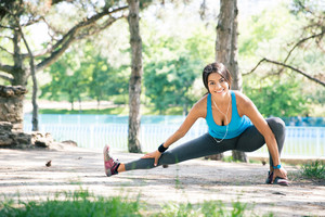 Fitness woman doing stretching exercise in park