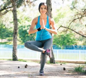 Happy sporty woman doing yoga exercises