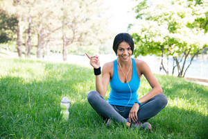 Happy fitness woman sitting on the green grass