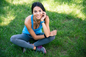Smiling fitness woman sitting on the green grass