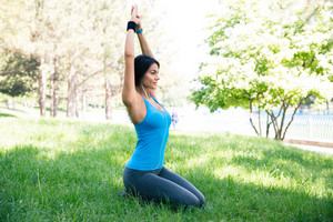 Woman doing yoga exercises on the green grass