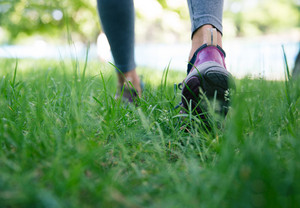 Footwear on female feet running on green grass