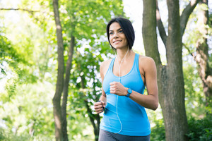 Happy sporty woman running outdoors