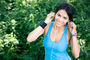 Happy sporty woman in headphones outdoors