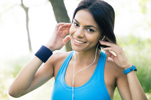 Smiling sporty woman in headphones outdoors