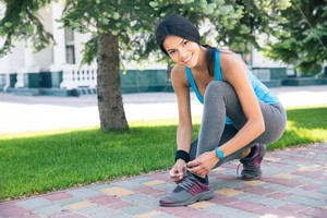 Smiling woman tying her shoelace outdoors