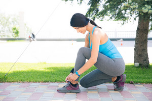 Woman tying her shoelace outdoors