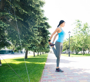 Sports woman stretching legs outdoors