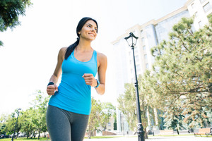 Happy young woman running outdoors