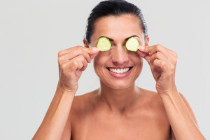 Happy woman covering her eyes with cucumber