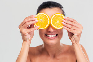 Smiling woman covering her eyes with orange