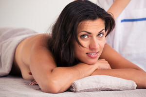 Happy woman lying on massage lounger