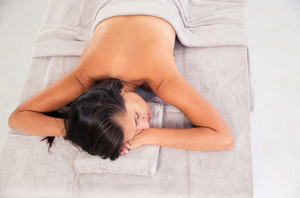 Young woman sleeping on massage lounger