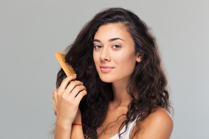 Happy cute woman combing her hair