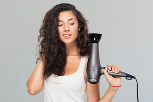Smiling young woman holding hairdryer