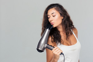 Pretty woman blowing on hairdryer