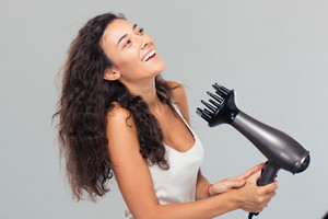 Laughing woman dries her hair