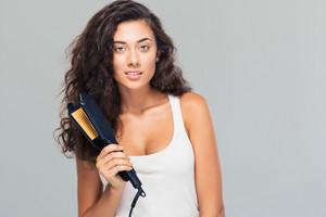 Lovely woman holding hair straightener