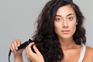 Woman doing hairstyle with hair straightener