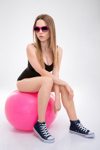 Modern style dancer posing on pink fitball