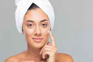 Woman with towel on head applying cream on face