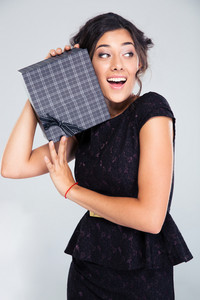 Attractive woman in black dress holding gift box