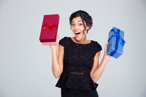 Woman in black dress holding two gift boxes