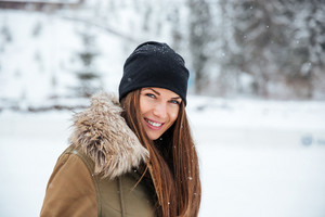 Smiling woman looking at camera outdoors